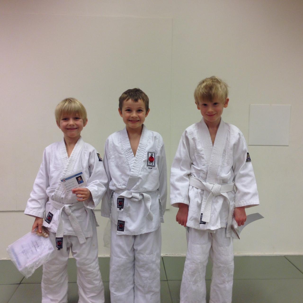 Tre glada barn från nybörjargruppen som graderade till sitt första streck i Ju-jutsu kai.